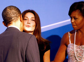 President Obama greets Carla Bruni, wife of French President Sarkozy, before the opening dinner for G20 leaders in Pittsburgh  — as US First Lady looks on (making you wonder a bit just how much trouble the President might be in later ... but not seriously, of course)!