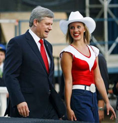 Canadian Prime Minister Stephen Harper is escorted off the stage by a dancer at the opening ceremonies for the World Skills Competition in Calgary, September 1, 2009. REUTERS/Todd Korol.