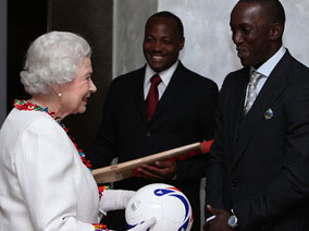 Queen happily receives autographed cricket bat from Brian Lara and autographed football from Dwight Yorke. Commonwealth Secretariat.