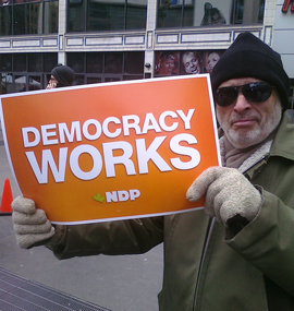Random demonstrator at January 23 No Prorogue rally on Dundas Square in Toronto pretends to enthusiastically hold sign handed out by NDP, while waiting for rally to finally begin. Photo WMW.