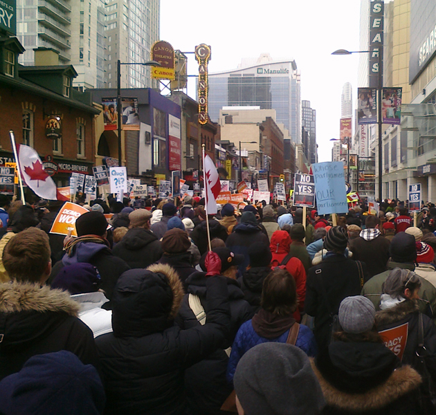 The crowd starts to move in Toronto, at last, led by police escort, inspired by drums, and chanting to keep warm. Photo WMW.