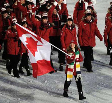 Athletes from host nation Canada march into BC Place at opening ceremony, with Clara Hughes carrying flag and wearing ancient Hudson 's Bay Company scarf. Photograph by Larry Wong / Canwest News Service.