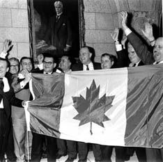 Members of Parliament celebrate inauguration of independent Canadian flag, at last, February 15, 1965.