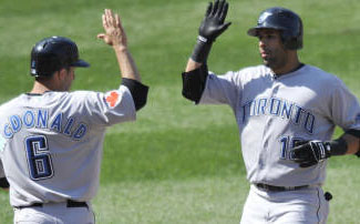 Blue Jays' Jose Bautista (r) is congratulated by John McDonald after hitting two-run homer during eighth inning against Baltimore Orioles, Sunday, April 11, 2010 in Baltimore. The  Jays won 5-2. AP Photo/Gail Burton.
