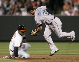 Jays' second baseman Mike McCoy (r) tags out Orioles' base runner Caesar Izturis  on a stolen base attempt, April 10. REUTERS/Joe Giza.