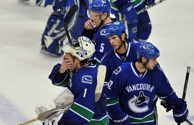 Vancouver Canucks defenceman Kevin Bieksa (second from right) has a consoling word for goalie Roberto Luongo as the Canucks await the post-series handshake after losing 5-1 to the visiting Chicago Blackhawks at GM Place on Tuesday, May 11, 2010.