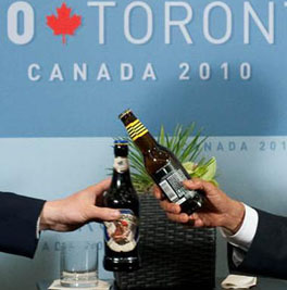 US President Barack Obama (r) and British Prime Minister David Cameron (l) clink bottles of beer as they settle a bet on the US-UK World Cup Soccer game, during meeting on sidelines of  G20 Summit in Toronto. SAUL LOEB/AFP/Getty Images.