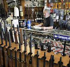 Ed Etheridge works behind a counter at Rink's Gun and Sport in the Chicago suburb of Lockport, Ill. Frank Polich / Reuters.